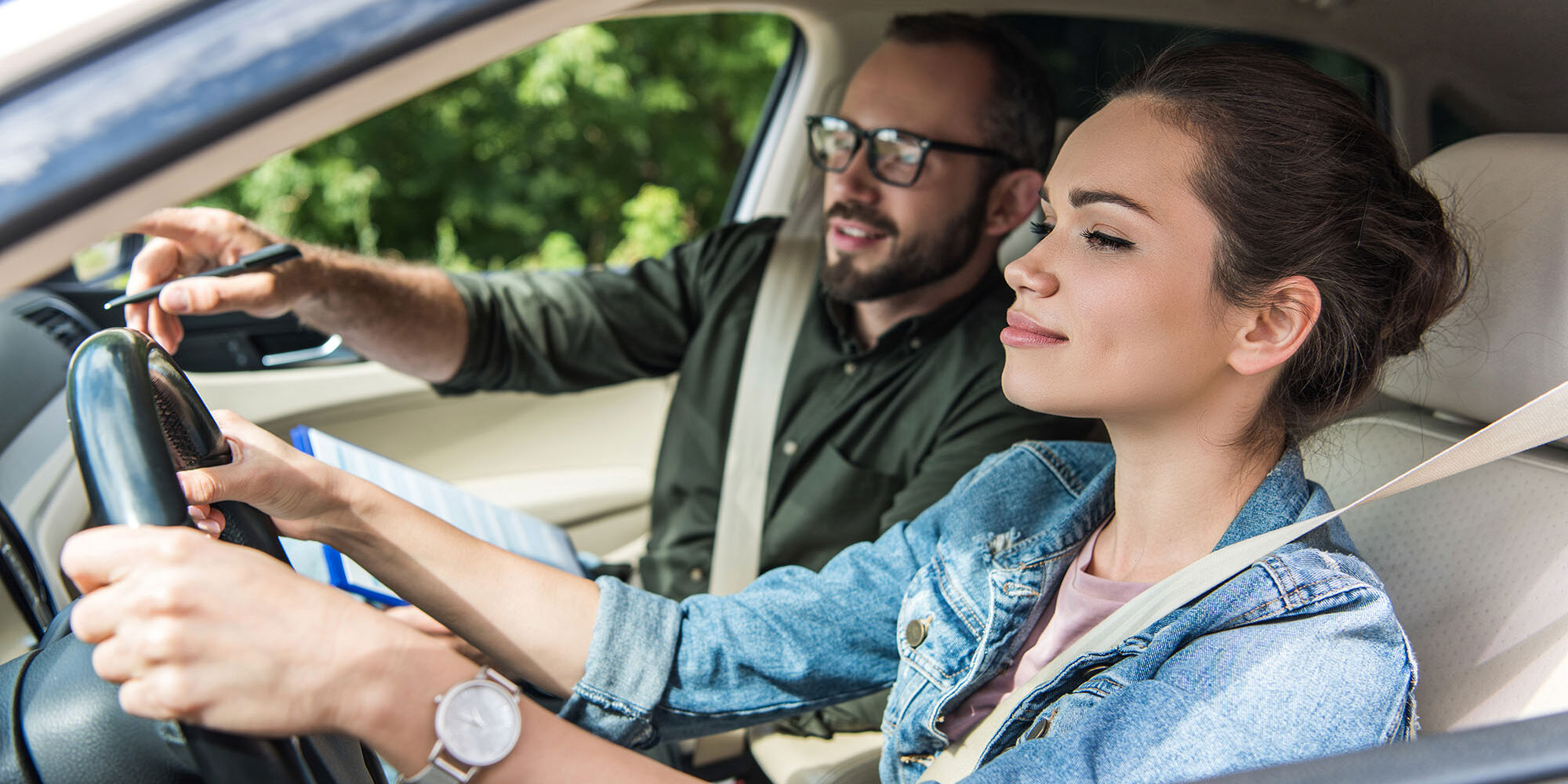 cheerful student and teacher in car at driving test